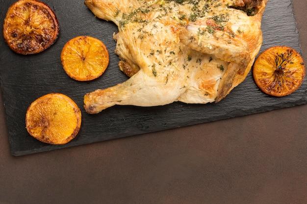 Bovenaanzicht gebakken kip op snijplank met stukjes sinaasappel