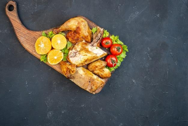 Bovenaanzicht gebakken kip tomaten schijfjes citroen op een houten bord met handvat op tafel