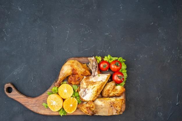 Bovenaanzicht gebakken kip tomaten schijfjes citroen op een houten bord