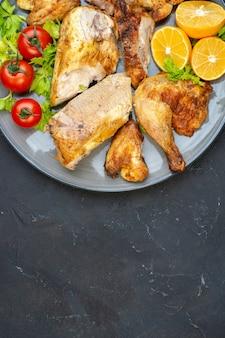 Bovenaanzicht gebakken kip verse tomaten schijfjes citroen op plaat op zwart