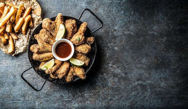Bovenaanzicht gebakken kippenvleugels chilisaus limoen en aardappelfrietjes.