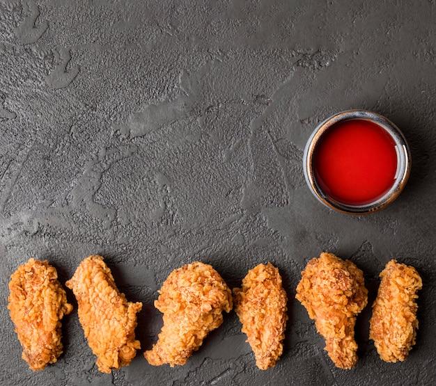 Bovenaanzicht gebakken kippenvleugels met saus en kopie-ruimte