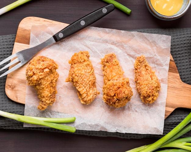 Bovenaanzicht gebakken kippenvleugels op snijplank met groene uien en vork