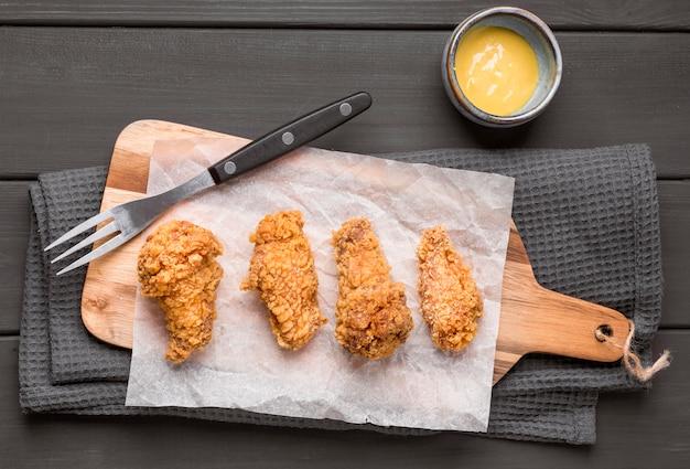 Bovenaanzicht gebakken kippenvleugels op snijplank met saus