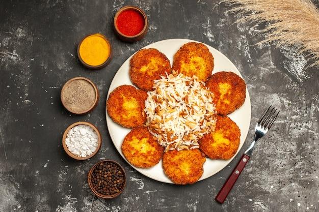 Bovenaanzicht gebakken koteletten met gekookte rijst en kruiden op donkere ondergrond voedsel schotel foto vlees
