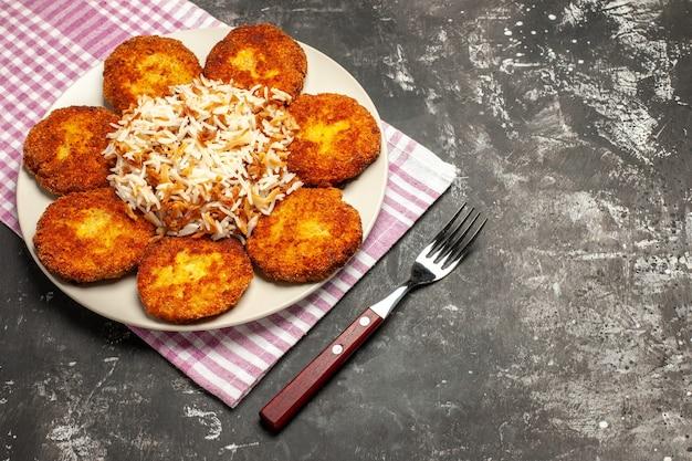 Bovenaanzicht gebakken koteletten met gekookte rijst op donkere vloer vlees rissole gerecht