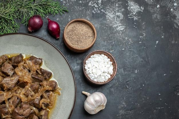 Bovenaanzicht gebakken lever en ui op bord dennenboomtak zeezout en peper knoflook