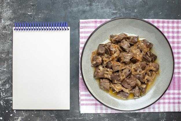 Bovenaanzicht gebakken lever en ui op bord op tafelkleed