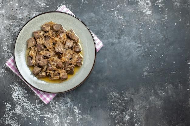 Bovenaanzicht gebakken lever en ui op ovale plaat op keukenhanddoek