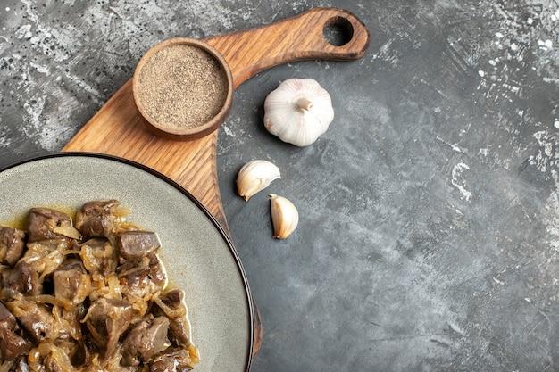 Bovenaanzicht gebakken lever en ui op plaat zwarte peper op snijplank knoflook op grijze tafel