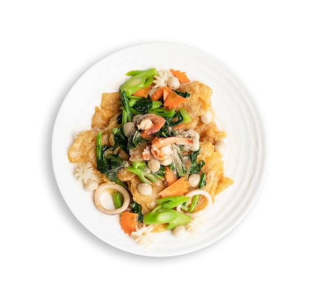 Bovenaanzicht. gebakken noedels met zeevruchten en groente in ronde witte schotel die op wit wordt geïsoleerd. thais eten concept