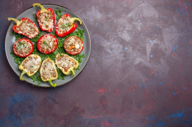 Bovenaanzicht gebakken paprika met kaasgroenten en vlees in de plaat op de donkere achtergrond bakmaaltijd diner schotel eten