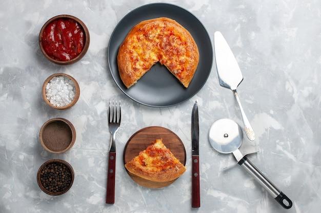 Bovenaanzicht gebakken pizza gesneden met kaas en verschillende kruiden op wit