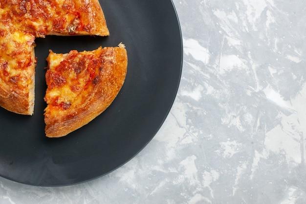 Bovenaanzicht gebakken pizza gesneden met kaas op wit