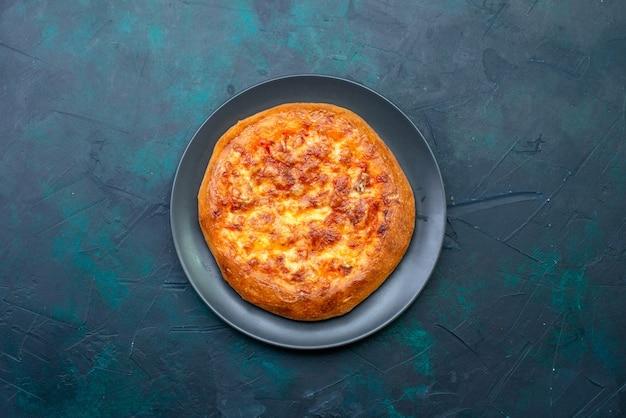 Bovenaanzicht gebakken pizza in plaat op donker