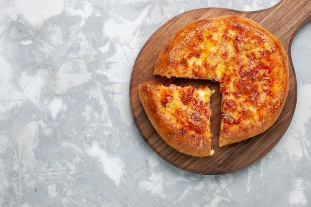 Bovenaanzicht gebakken pizza met kaas op licht wit