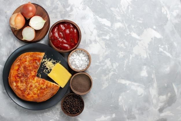 Bovenaanzicht gebakken pizza met verschillende kruiden op licht bureau