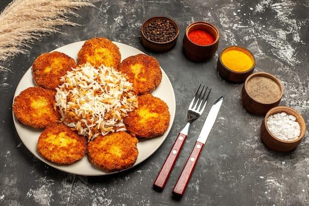 Bovenaanzicht gebakken schnitzels met gekookte rijst en kruiden op donkere bureau foto-vleesgerecht