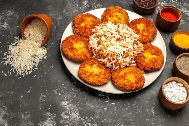 Bovenaanzicht gebakken schnitzels met gekookte rijst en kruiden op donkere ondergrond fotovoedsel vleesgerecht