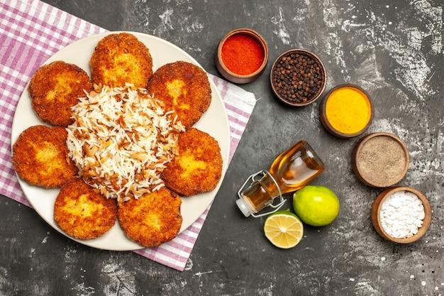 Bovenaanzicht gebakken schnitzels met gekookte rijst en kruiden op donkere ondergrond voedsel vlees rissole