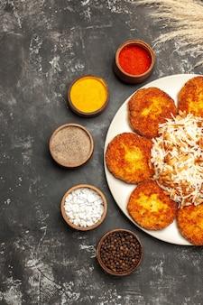 Bovenaanzicht gebakken schnitzels met gekookte rijst en kruiden op donkere vloer schotel foto vlees