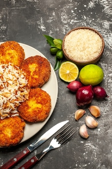 Bovenaanzicht gebakken schnitzels met gekookte rijst op de donkere oppervlak vleesvoedsel gerecht rissole