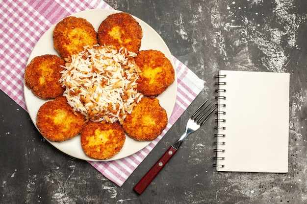 Bovenaanzicht gebakken schnitzels met gekookte rijst op de donkere plaat vleesgerecht