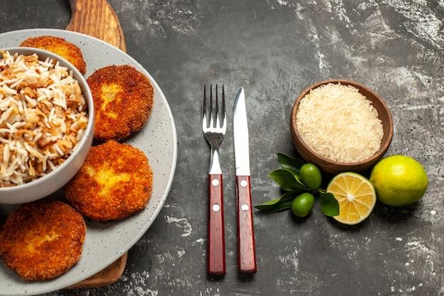 Bovenaanzicht gebakken schnitzels met gekookte rijst op donkere vloer schotel vlees rissole