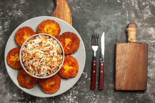 Bovenaanzicht gebakken schnitzels met gekookte rijst op het donkere oppervlak gerecht vlees rissole