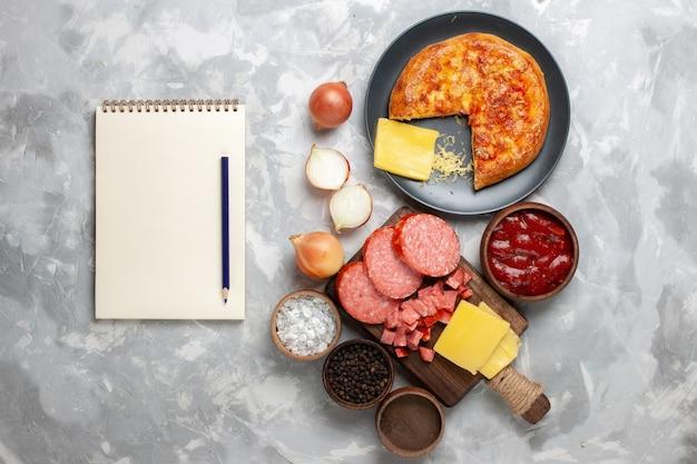 Bovenaanzicht gebakken smakelijke pizza met verschillende kruiden en worst op wit