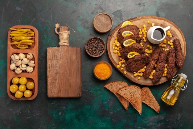 Bovenaanzicht gebakken smakelijke schnitzels met likdoorns broodbroodjes en kruiden op groen bureau vleesmaaltijd eten groenten koken