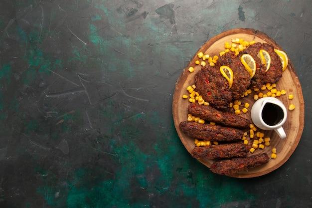 Bovenaanzicht gebakken smakelijke schnitzels met likdoorns op donkergroen bureau vleesmaaltijd eten groente koken