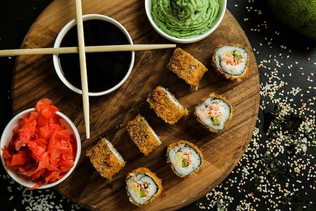 Bovenaanzicht gebakken sushi rolt op een stand met gembersojasaus en wasabi met stokjes