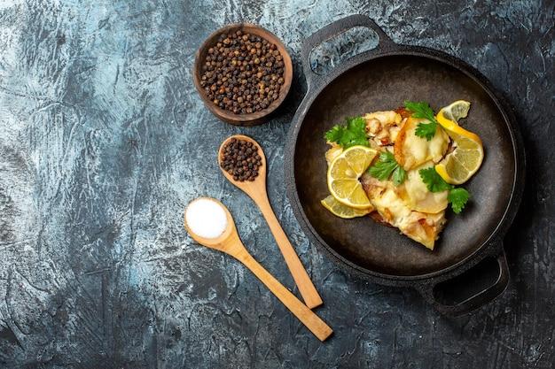 Bovenaanzicht gebakken vis in pan met citroen en peterselie kruiden in houten lepels zwarte peper in houten kom op grijze achtergrond