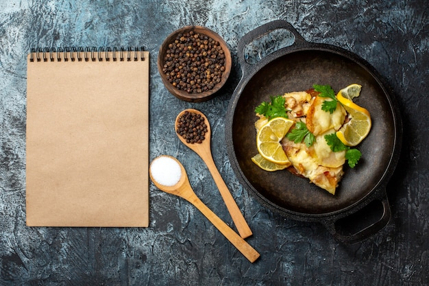 Bovenaanzicht gebakken vis in pan met citroen en peterselie kruiden in houten lepels zwarte peper in kom notitieboekje op grijze achtergrond Gratis Foto