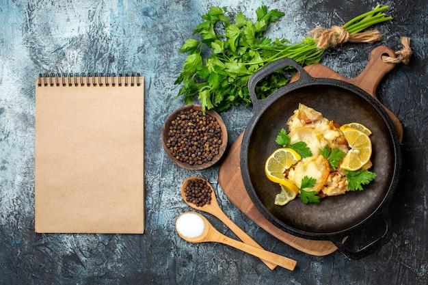 Bovenaanzicht gebakken vis in pan met citroen en peterselie kruiden in houten lepels