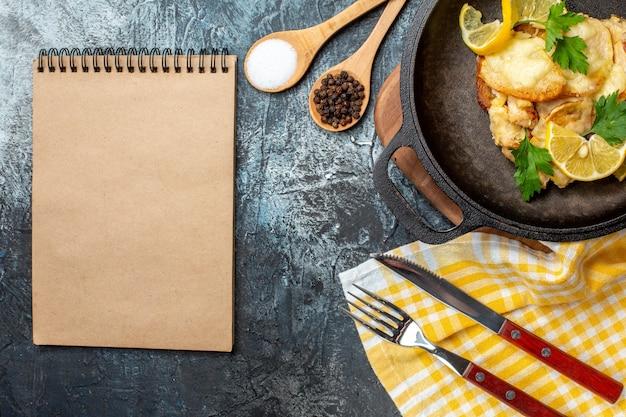 Bovenaanzicht gebakken vis in pan met citroen en peterselie kruiden in kom en houten lepels vork en mes kladblok op grijze achtergrond
