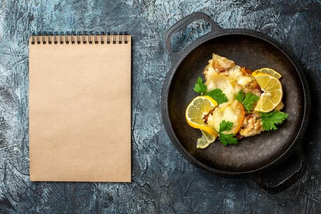 Bovenaanzicht gebakken vis in pan met citroen en peterselie notitieboekje op grijze achtergrond