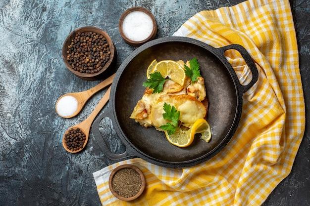 Bovenaanzicht gebakken vis in pan met citroen en peterselie op geel wit geruit tafelkleed