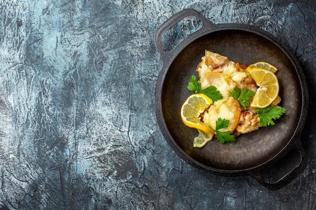 Bovenaanzicht gebakken vis in pan met citroen en peterselie op grijze achtergrond