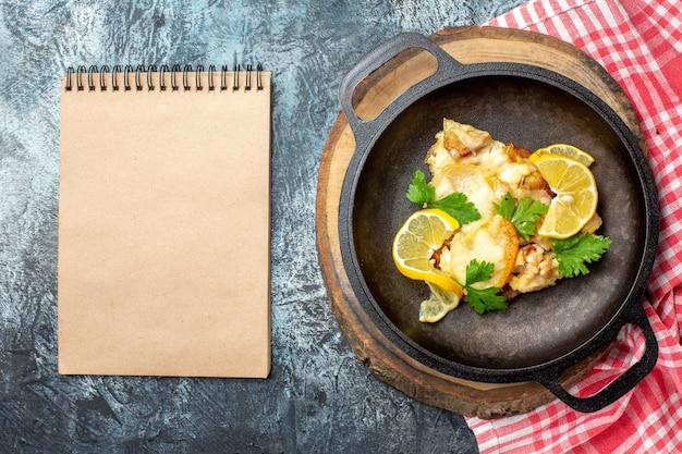 Bovenaanzicht gebakken vis in pan op houten bord notebook op grijze achtergrond