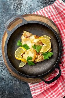 Bovenaanzicht gebakken vis in pan op houten bord op grijze achtergrond