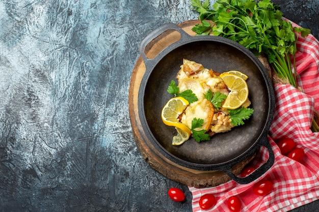 Bovenaanzicht gebakken vis in pan op houten bord