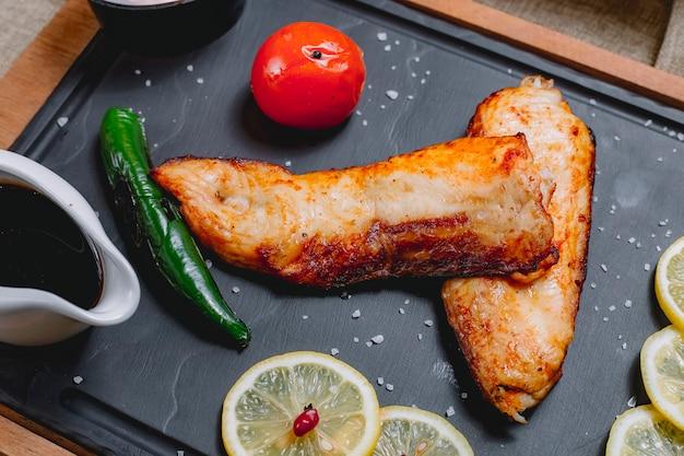 Bovenaanzicht gebakken vis met groenten en plakjes citroen en granaatappelsaus