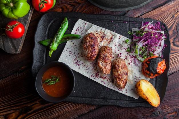 Bovenaanzicht gebakken vlees met gebakken aardappelen en tomaat en uien en pikante saus in donkere plaat
