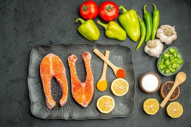 Bovenaanzicht gebakken vlees plakjes met kruiden en verse groenten op de donkere achtergrond