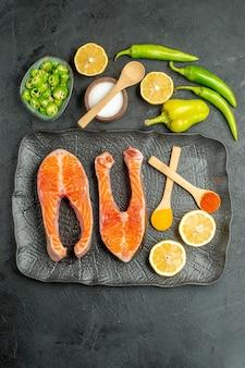 Bovenaanzicht gebakken vlees plakjes met paprika en citroen op de donkere achtergrond