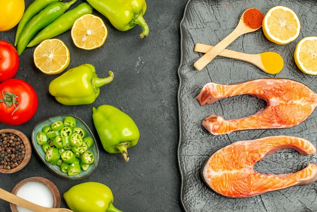 Bovenaanzicht gebakken vlees plakjes met verse groenten op de donkere achtergrond