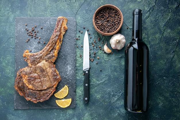 Bovenaanzicht gebakken vleesplak met schijfjes citroen en peper op donkere achtergrond vlees koken rib diner eten gerecht bak dier