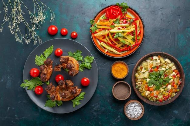 Bovenaanzicht gebakken vleesplakken met groentesoep en kruiderijen op donkerblauw bureau groente maaltijd eten vlees diner gezondheid